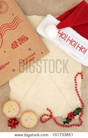 Christmas eve letter to santa with ho ho ho red hat, mince pie cakes, parcel package and decorations over parchment and brown paper background.