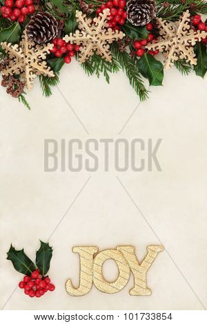 Christmas background border with gold joy sign, snowflake bauble decorations, holly and winter greenery over old parchment paper.