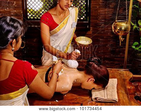 Woman having ayurvedic massage with pouch of rice. Three people.