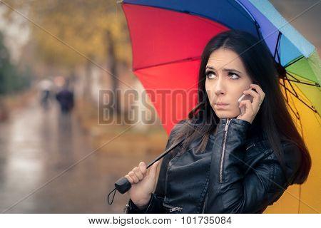 Autumn Girl Holding a Rainbow Umbrella and a Smartphone