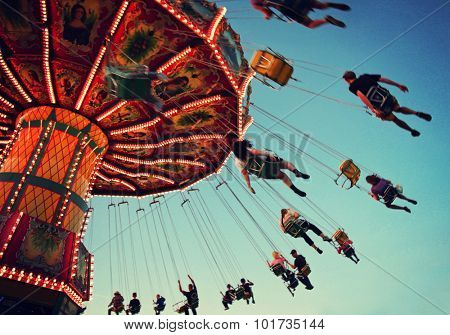 a swinging fair ride at dusk toned with a retro vintage instagram filter app or action with motion blur and grainy effect added for a grunge look and feel
