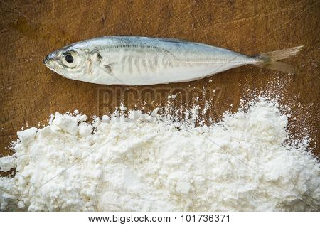 Floury fish on a wooden background. Close up