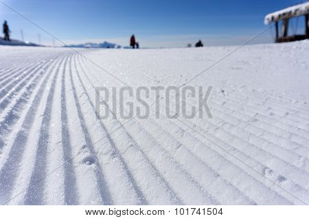 Fresh snow groomer tracks on a mountain ski piste