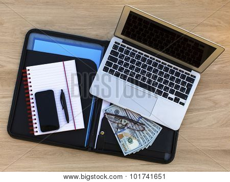 Business concept - folder for documents, laptop, glasses, Notepad with pen and hundred-dollar bills - a top view on the table of expensive wood.