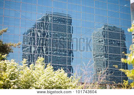 Office Buildings Reflecting In Glass Wall Of Other Building