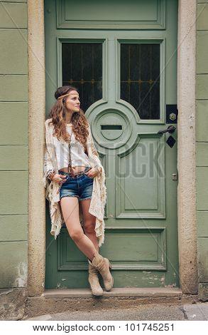 Pensive Hippy-looking Woman Standing Outdoors Against Door