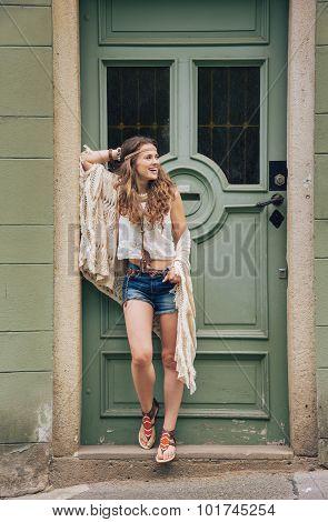 Happy Hippy-looking Woman Standing Outdoors Against Wooden Door