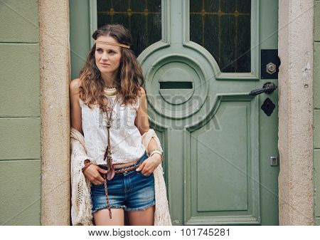 Portrait Of Trendy Hipster Woman Standing Outdoors Against Door