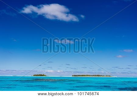Stunning tropical islands with palm trees, white sand, turquoise ocean water and blue sky at Cook Islands, South Pacific