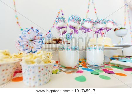 Colorful decoration of kids birthday party table with popcorn and sweets