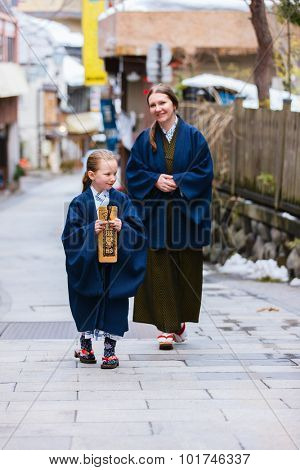 Family wearing yukata traditional Japanese kimono at street of onsen resort town in Japan. Translation of text on wooden plate: passport for round bath visit to protect you from bad luck.