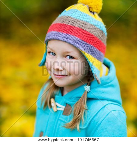 Adorable little girl in colorful hat and coat outdoors at beautiful autumn park