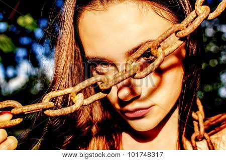Beautiful Teenage Girl Looking Through The Hole Of A Rusty Chain