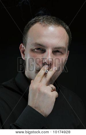 Young Man Smokes A Cigarette
