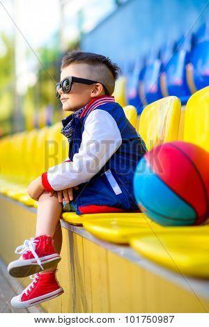 Stylish  little boy posing at basketball court