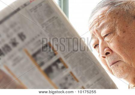 A Senior Man Is Reading Newspaper