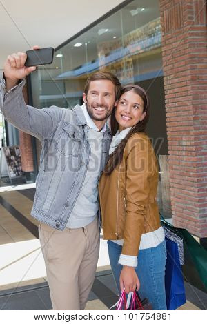 Young happy couple taking a selfie in front of a store