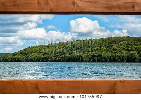 Landscape of beautiful lake in the summer. View through a wooden frame from pier. Vacation and holid