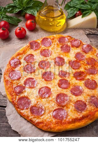 Traditional Italian pizza pepperoni with delicious crust on vintage wooden table background