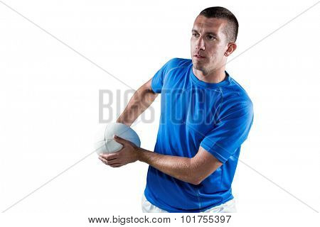 Rugby player looking away while holding ball against white background