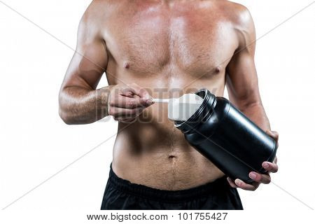 Midsection of shirtless man scooping up protein powder on white background