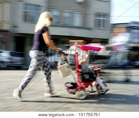 Young Family With Small Child And A Stroller Walking Down The Street. Intentional Motion Blur