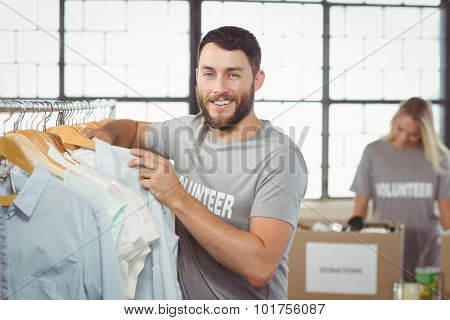 Portrait of happy man selecting clothes for donation with woman man in background