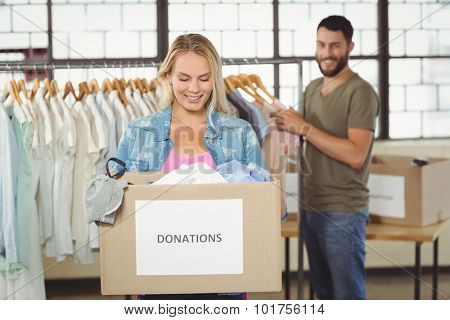 Woman holding donation box while standing in creative office