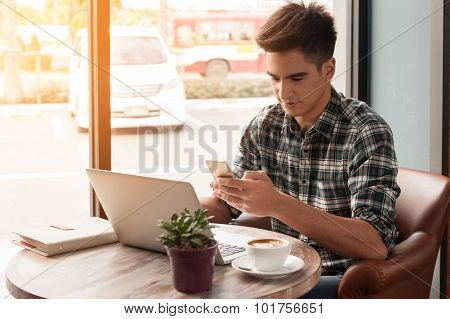 Businessman Using Smartphone And Laptop Writing On Tablet On Wooden Table In Coffee Shop With A Cup