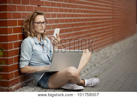 Upset or worried student wornikg with laptop next to the brick wall.