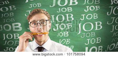 Geeky businessman biting a pencil against green chalkboard
