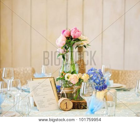 Table decoration with peonies and roses in rustic style