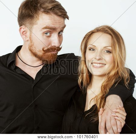 young hipster couple fooling around on white background close up