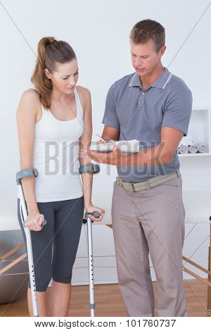 Woman with crutch speaking with his doctor in medical office