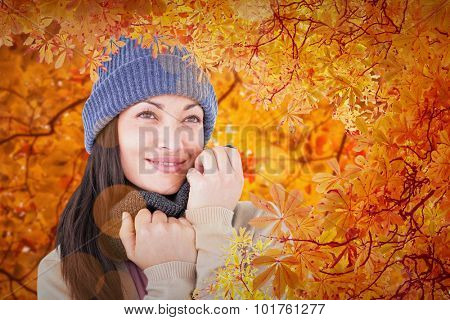 Attractive brunette looking up wearing warm clothes against autumn scene