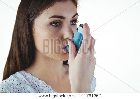 Asthmatic brunette using her inhaler on white background