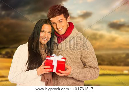 Young couple holding a gift against country scene