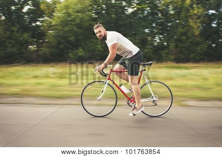 Young Bearded Hipster Driving Bicycle