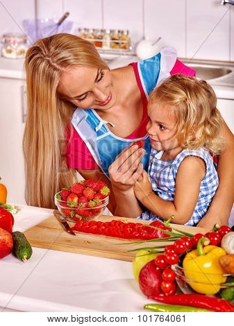 Happy child feed mother  at kitchen.