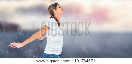 Side view of relaxed woman with arms outstretched against calm sea with lighthouse