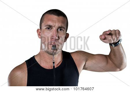 Portrait of attentive trainer blowing his whistle against white blackground