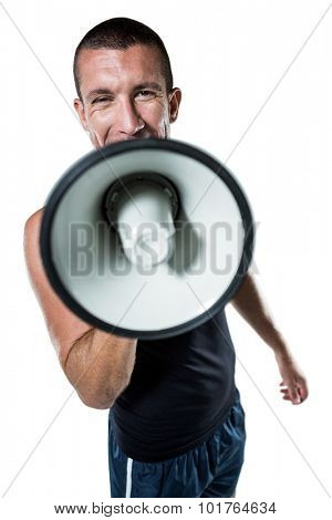 Portrait of male trainer yelling through megaphone against white background
