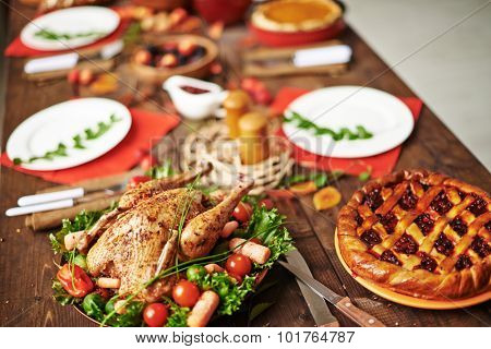 Homemade pie and roasted chicken on served Thanksgiving table