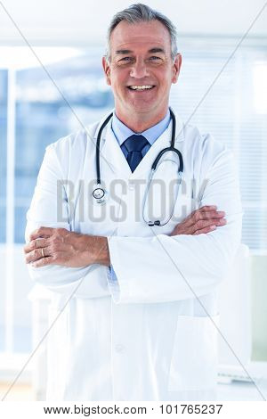 Portrait of male doctor with arms crossed standing in hospital