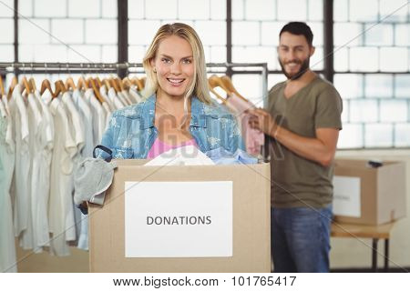 Portrait of woman holding donation box while standing in creative office