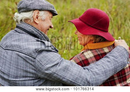 Back view of affectionate seniors interacting in natural environment