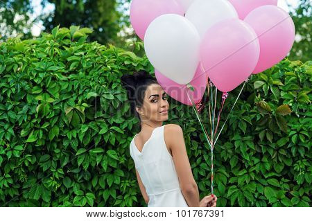 attractive girl with balloons standing next to a hedgerow