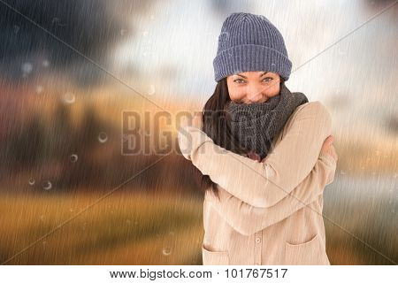Attractive brunette looking at camera wearing warm clothes against country scene