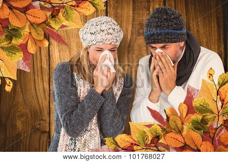 Couple sneezing in tissue against wooden table