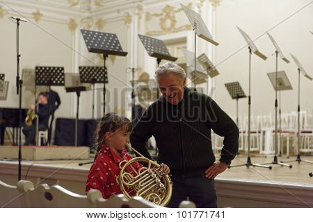 ST. PETERSBURG, RUSSIA - SEPTEMBER 7, 2015: Virtuoso horn player Hermann Baumann (right) and a girl with French horn on the rehearsal during the International festival of French horn